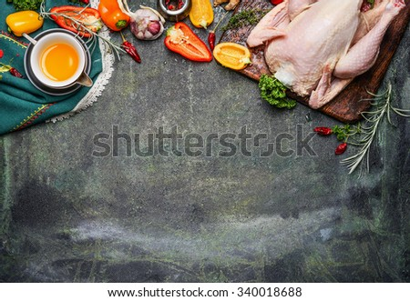 Raw whole chicken with oil and vegetables ingredients for tasty cooking on rustic background, top view, border.  Healthy food or diet eating concept. - stock photo
