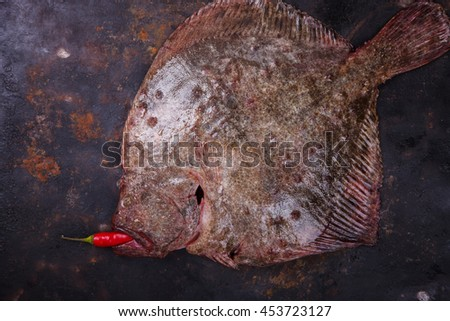 Raw whole flounder fish with spices,  onion on dark background , top view.Healthy food concept.Copy space. selective focus.