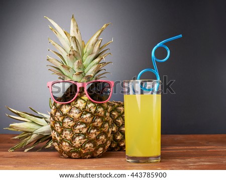 Raw whole pineapple in red sunglasses with a glass of juice on wooden brown surface table - stock photo