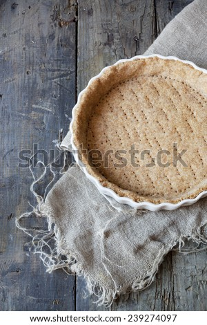 raw wholemeal dough for tart on ceramic mold for quiche on wooden table with napkin