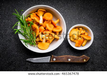 Raw wild chanterelle mushrooms in a bowls on a black background