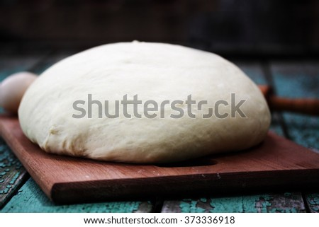 Raw yeast dough on a wooden board - stock photo