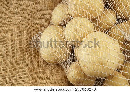 raw young potatoes in net pack on burlap background - stock photo