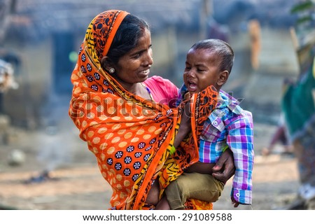 RAXAUL, INDIA - NOV 8: Unidentified Indian woman with her child on Nov 8, 2013 in Raxaul, Bihar state, India. Bihar is one of the poorest states in India. The per capita income is about 300 dollars. - stock photo