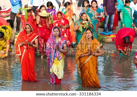 RAXAUL, INDIA - NOV 8: Unidentified Indian women celebrating Chhath by standing in a river and offering prashad (prayer offerings) to the setting sun on Nov 8, 2013 in Raxaul, Bihar state, India.  - stock photo