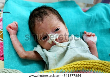 RAXAUL, INDIA - OCT 21: Unidentified newborn baby in a local hospital on Oct 21, 2011 in Raxaul, Bihar, India. Bihar is one of the poorest states in India. The per capita income is 300 dollars. - stock photo