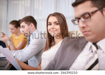 Ray of happiness. Selective focus on a young attractive business woman sitting around her gloomy colleagues in blurry - stock photo