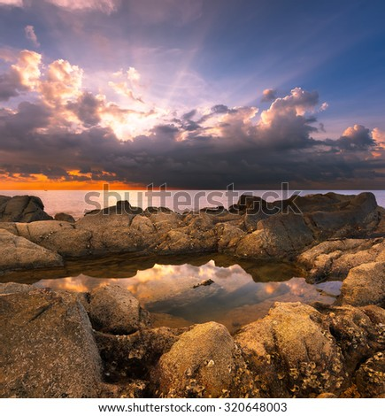 Ray of light over the sky with reflection of the sky over the water in the rock formation.Beach are located in Sabah,Borneo