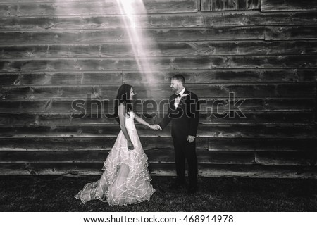 Ray of sun lies between beautiful wedding couple posing before a wooden hangar