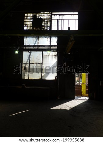 ray of sunlight entering through the open door of an industrial hall and brightness in a dirty window - stock photo