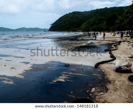RAYONG -JUL 31: Crude oil stain at Aou Prow beach in Rayong, Thailand on Jul 31, 2013. 50 tons of crude oil accidentally leaked during transferring from tanker on July 27 caused evironmental disaster. - stock photo