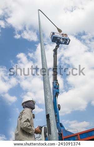 RAYONG , THAILAND , DECEMBER 26 - 2014 ; Electrical technician repairing street light by boom lift in industrial Plant at Rayong, Thailand
