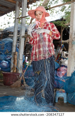RAYONG, THAILAND - JULY 26 : Unidentified Fisherman cleaning and repairing fishnet on July 26, 2014 at Lammaepim Bay Rayong, Thailand.