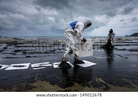 RAYONG, THAILAND - JULY 31, 2013: Workers remove crude oil spilled from Prao Bay on July 31, 2013 in Samet Island, Rayong, Thailand