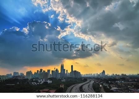 Rays of light atop city skyline in Kuala Lumpur Malysia - stock photo