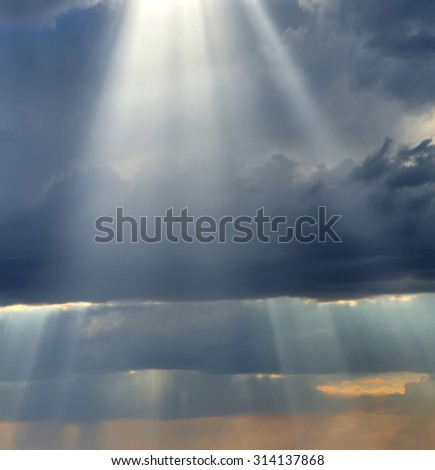 Rays of light shining down in the evening - stock photo