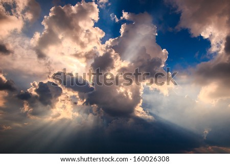 Rays of light shining through dark clouds for background - stock photo