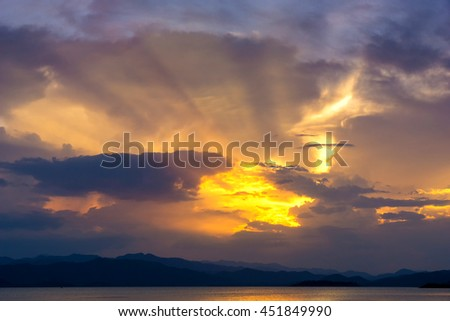 Rays of light shining through the clouds over the dam - stock photo