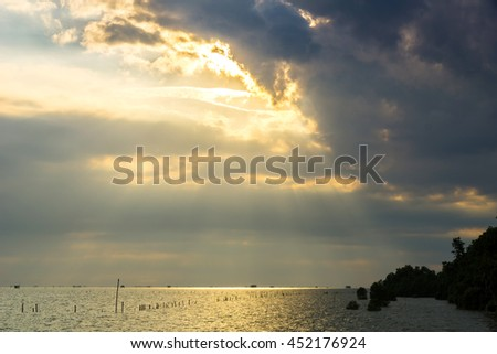 Rays of light shining through the clouds to the sea - stock photo