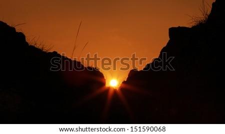 Rays of light - sunrise behind rocks - stock photo