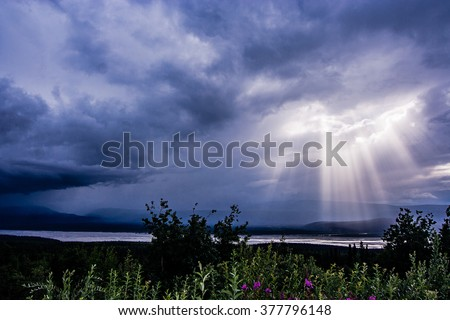 Rays of sun beam through a dramatic cloud of sky and illuminate the glacial Delta River in the Alaska Range mountains - stock photo