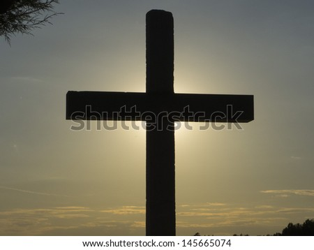 Rays of the sun behind a Holy Cross. - stock photo