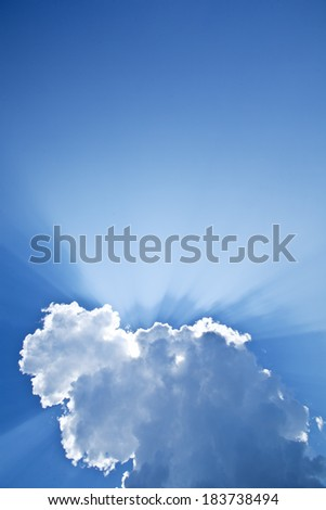 Rays of the sun peeking from behind the clouds. - stock photo