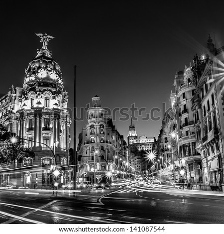 Rays of traffic lights on Gran via street, main shopping street in Madrid at night. Spain, Europe. Black and white photo. - stock photo