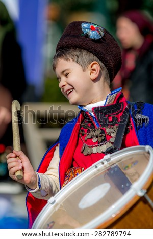 """RAZLOG, BULGARIA - APRIL 13, 2015: A small smiling Bulgarian boy playing on drums on the stage during the traditional folklore festival """"1000 national costumes"""" - stock photo"""