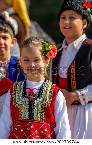 """RAZLOG, BULGARIA - APRIL 13, 2015: A smiling Bulgarian girl in a folklore costume during the traditional folklore festival """"1000 national costumes"""" - stock photo"""