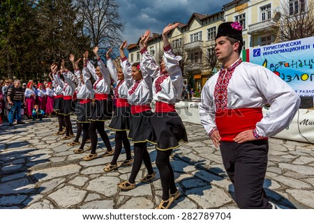 """RAZLOG, BULGARIA - APRIL 13, 2015: Bulgarian folklore dancers performing a round dance during the traditional folklore festival """"1000 national costumes"""" - stock photo"""