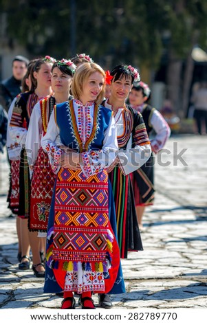 """RAZLOG, BULGARIA - APRIL 13, 2015: Female Bulgarian folklore dancers in a line during the traditional folklore festival """"1000 national costumes"""" - stock photo"""