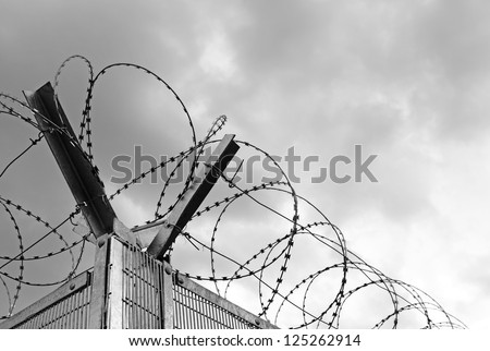 Razor barbed wire on a metal prison fence against a gloomy rain cloud sky. - stock photo