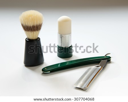 Razor, shaving brush and soap on a white background