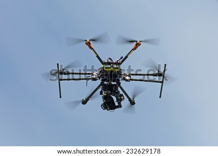 RC helicopter (multicopter or drone) with a camera in the sky - stock photo
