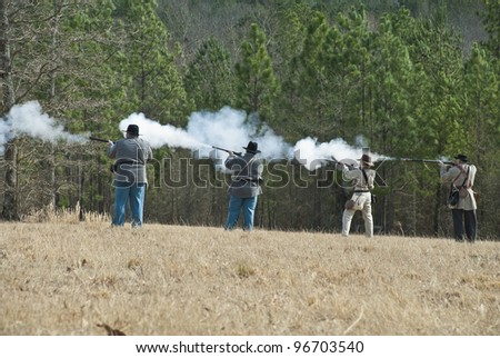Re-enactors form a skirmish line and fire muskets and rifles. - stock photo