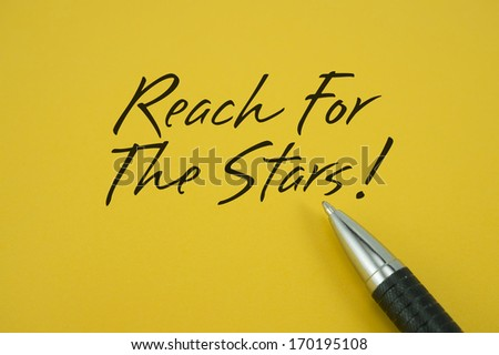 Reach For The Stars note with pen on yellow background - stock photo