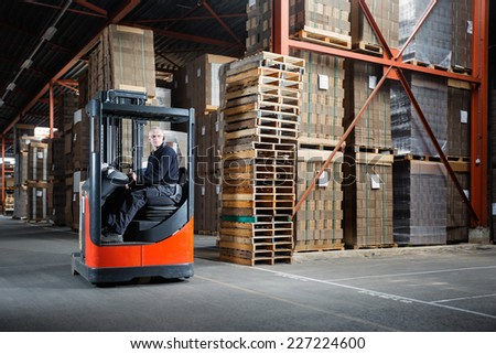 Reach truck driver in a warehouse where pallets and cardboards are stored - stock photo