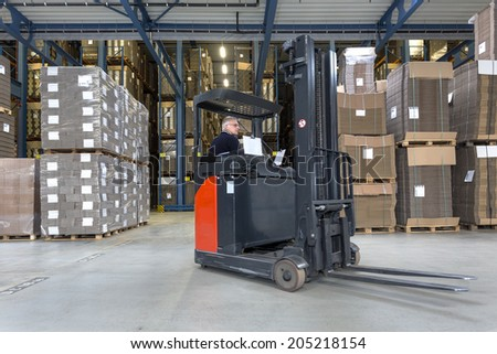 Reach truck driving around cartboard boxes in a warehouse.  - stock photo