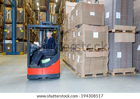 Reach truck forklift driving past an isle in a warehouse at speed. A panned image, with stock and cardboard boxes in the shelves of the storage racks. Conceptual image about internal logistics