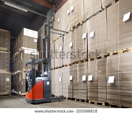 Reach truck forklift lifting a pallet from the top shelf in a large warehouse. - stock photo
