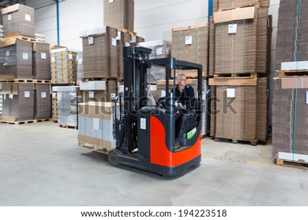 Reach truck passing by in a warehouse where cartboard boxes are stored on palets. - stock photo