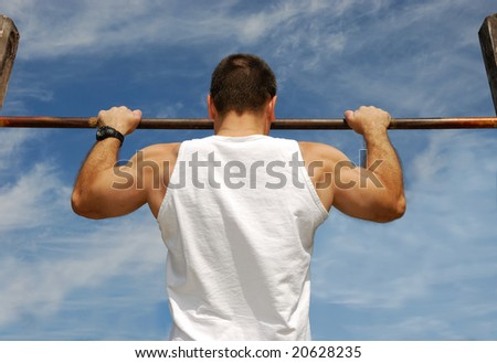 Reaching Goal: Strong man doing pull-ups on a bar in a park - stock photo