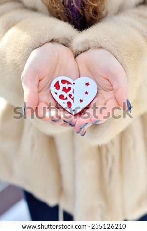 Read heart in white warm wool gloves. - stock photo