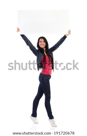 Read my message. An attractive woman holding empty placard over her head. Full length studio shot isolated on white. - stock photo