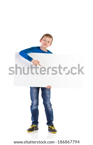Read this! Schoolboy holding white blank banner and pointing. Full length studio shot isolated on white. - stock photo