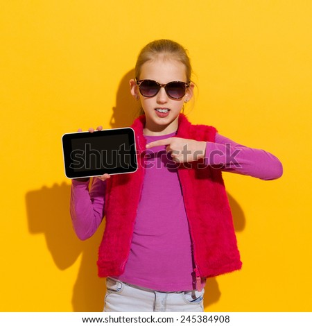 Read this. Young blond girl pointing at a blank digital tablet screen. Waist up  studio shot on yellow background. - stock photo