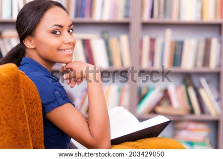 Reading a book in library. Rear view of beautiful African female student holding a book and looking over shoulder while sitting at the chair in library - stock photo