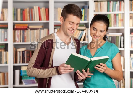 Reading a book together. Cheerful young man and woman reading book together while standing clode to each other in the library