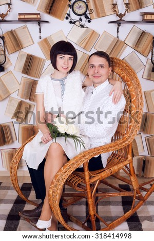 Reading a book together. Cheerful young man and woman reading book together while standing clode to each other in the library - stock photo
